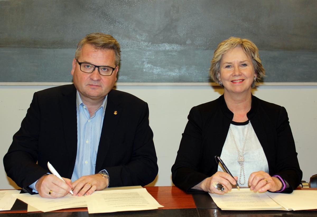 Lárus Blöndal, forseti ÍSÍ, og Kristín Ingólfsdóttir, rektor HÍ, undirrita samninginn í húsakynnum háskólans.