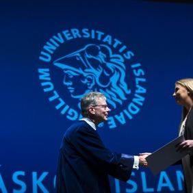 Rektor Háskóla Íslands tekur í höndina á kandídat við brautskráningu.