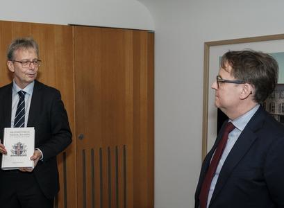 """Jón Atli Benediktsson, rektor Háskóla Íslands, afhendir Benedikt Bogasyni, forseta Hæstaréttar, ritið """"Hæstiréttur og Háskóli Íslands: Rit til heiðurs Hæstarétti 100 ára""""."""