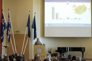 Unnur Anna Valdimarsdóttir í pontu, í bakgrunn súlurit og mynd af Íslandi